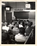 Classroom of students watching demonstration of closed-circuit TV